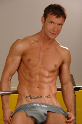 Sporty hunk jerking off after working out